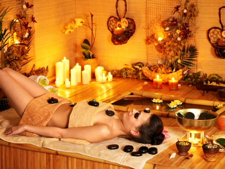 Woman getting stone therapy massage in bamboo spa. photo