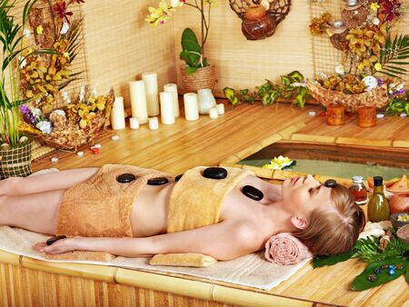 day spa: Woman getting stone therapy massage in bamboo spa.