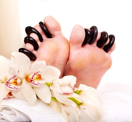 pedicura: Una mujer recibe masaje con piedras calientes en los pies. Aislado.