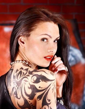 body paint sexy: Woman with body art aganist graffiti brick wall.