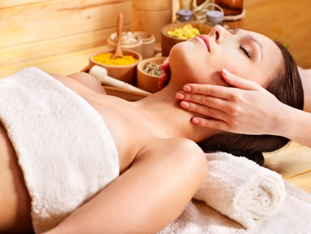 aromatherapy oils: Woman getting facial  massage in wooden spa.