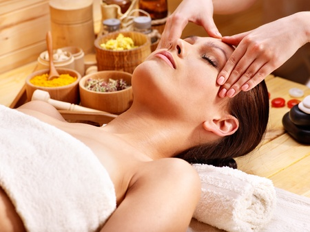 day spa: Woman getting facial  massage in wooden spa.