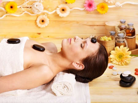 Woman getting stone therapy massage in wooden spa. Stock Photo - 13309598