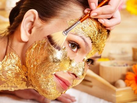 Kobieta coraz złoty twarzy maskę. Zdjęcie Seryjne