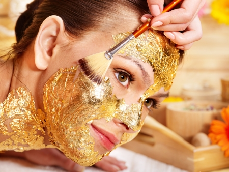 facial spa: Woman getting  gold facial mask.