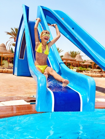 Child on water slide at aquapark. Summer outdoor. photo