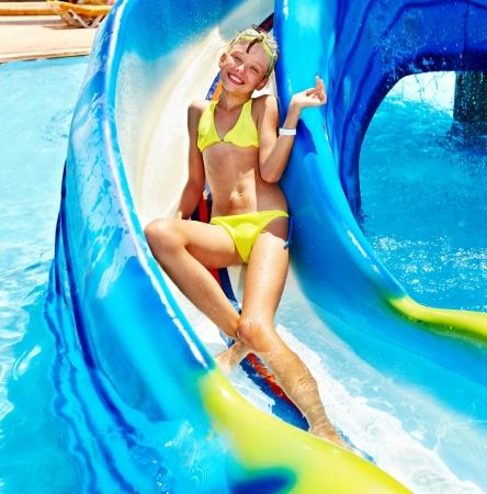 child in bikini: Child on water slide at aquapark. Summer outdoor.