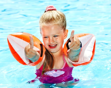 Child with armbands playing in swimming pool. Summer outdoor. photo