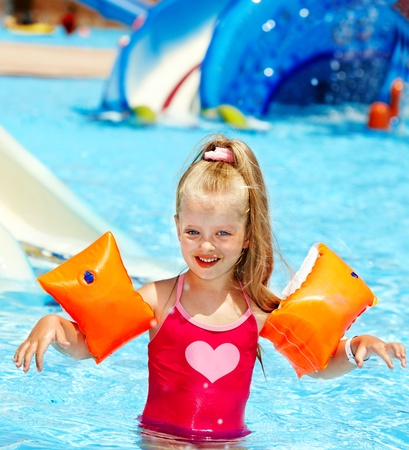 Child with armbands playing in swimming pool. Summer outdoor. Stock Photo - 13563210