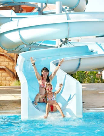 bikini pool: Child with mother on water slide at aquapark. Summer outdoor.
