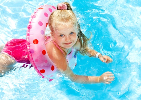 one piece swimsuit: Children playing in swimming pool. Summer outdoor.