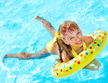 swimming to float: Child playing in swimming pool. Summer outdoor. Stock Photo
