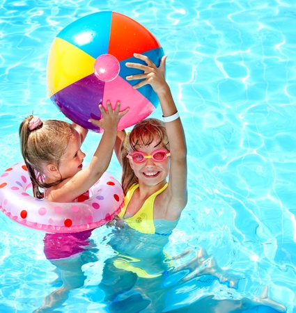 Child playing in swimming pool. Summer outdoor. photo