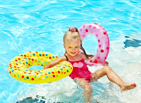 float tube: Child  swimming in pool. Summer outdoor.