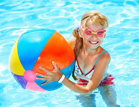 beach ball girl: Little girl swimming in pool. Stock Photo