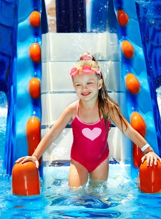 Little girl on water slide at aquapark. photo