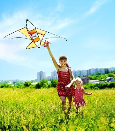 Group children flying kite outdoor. Summer outdoor.