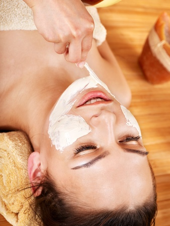 Girl having clay facial mask apply by beautician. photo