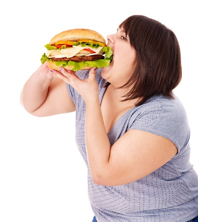Overweight woman eating hamburger. Isolated. photo