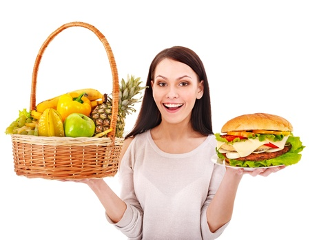 Woman choosing between fruit and hamburger. Isolated. Stock Photo - 13563237