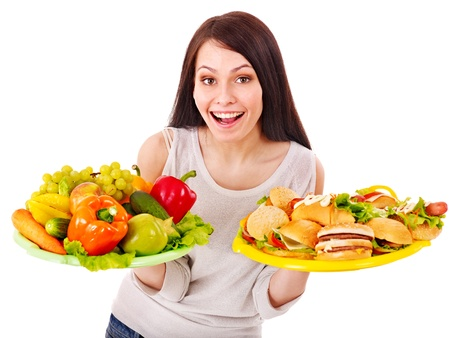 Woman choosing between fruit and hamburger. Isolated. Stock Photo - 13563039