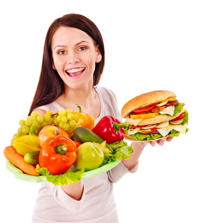 Woman choosing between fruit and hamburger. Isolated. photo