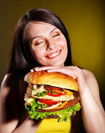 high calorie: Slim woman holding hamburger.