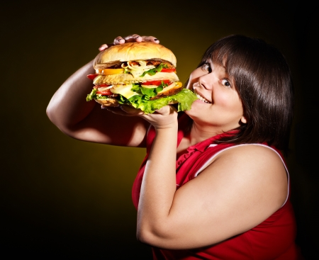 Overweight woman eating hamburger. Stock Photo - 13563148