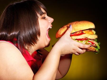 dog food: Overweight hungry woman eating hamburger.