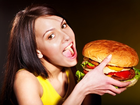 high calorie foods: Slim woman eating hamburger.