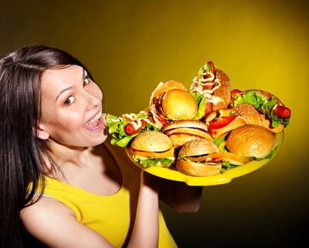 perro comiendo: Mujer delgada celebraci�n de la hamburguesa grupo.