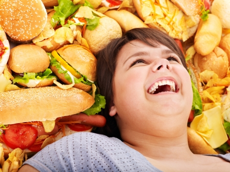 eating out: Happy overweight woman with fast food. Stock Photo