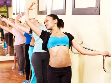 Women group in aerobics class do exercises . photo