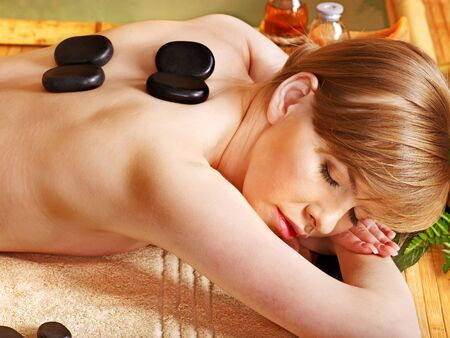 Woman getting relaxing stone therapy massage . photo