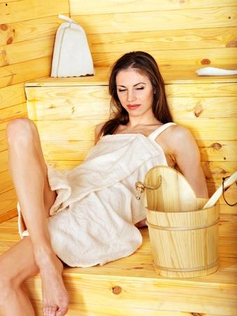 overheating: Young woman in sauna. Overheating danger.