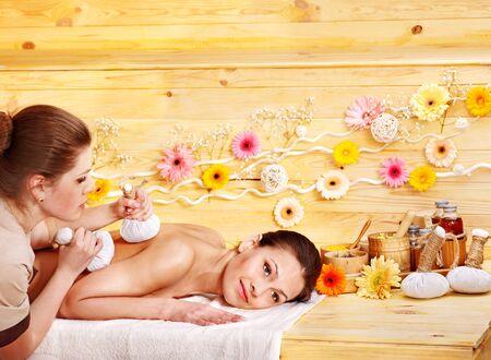 body oil: Woman getting herbal ball massage  in spa resort.