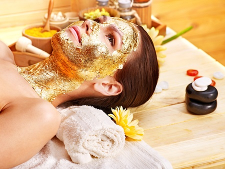 Woman getting  gold facial mask. photo