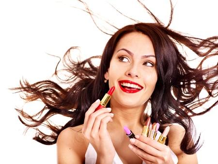 applying lipstick: Girl applying makeup. Girl chooses lipstick.