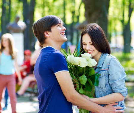 Couple of teenager on date outdoor. Group of people in background. Stock Photo - 13563208