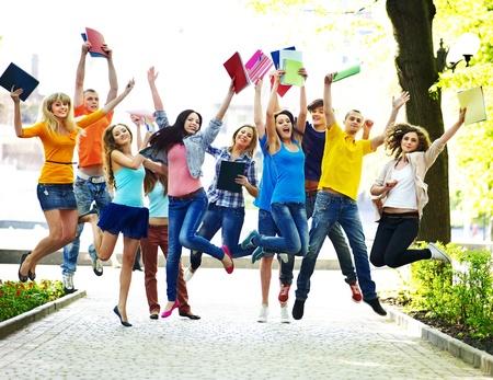 Grupo de estudiantes con portátil al aire libre de verano.