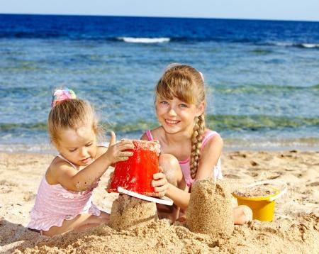 sandcastles: Little girl  playing on  beach.