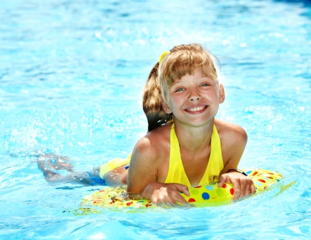 Child sitting on inflatable ring in swimming pool. photo