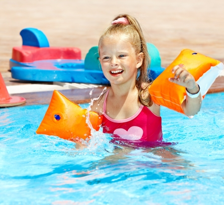 Child with armbands playing in swimming pool. Summer outdoor. Stock Photo - 13851933