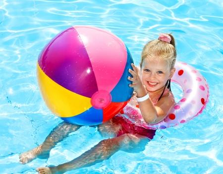 maillot de bain fille: Enfant assis sur un boudin gonflable dans la piscine. Banque d'images