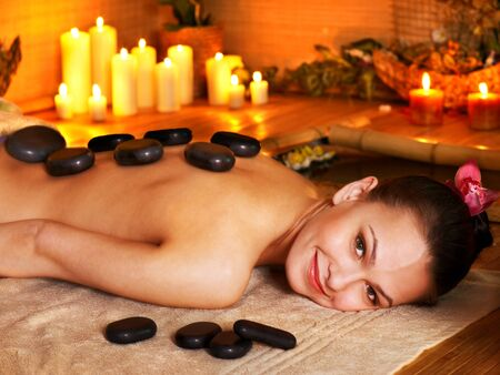 thai orchid: Woman getting stone therapy massage in bamboo spa.