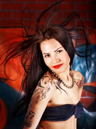 denim skirt: Woman with body art aganist graffiti brick wall.