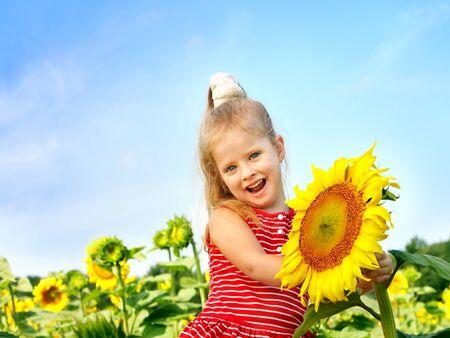 Happy child holding  sunflower summer outdoor. photo
