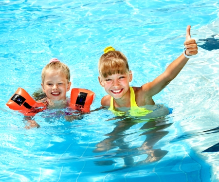 kids wear: Child with armbands in swimming pool. Summer outdoor.