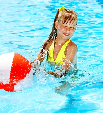 beach ball girl: Little girl playing ball in swimming pool.