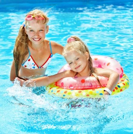 Los niños sentados en el anillo inflable en la piscina.